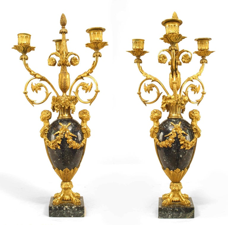 Pair of French (19th century) black marble and gilt bronze trim three-light. Candelabrum with extensive floral and swag designs as well as lion paw details (Signed: Henry Dasson, 1879).