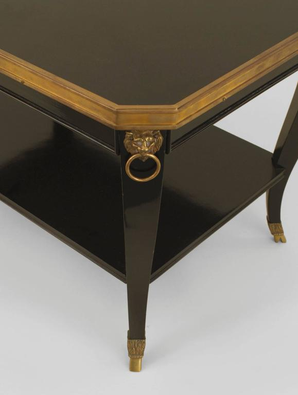 French 1940s (Regency style) ebonized rectangular top coffee table with a shelf and bronze top edge with lion head trim and hoof feet (stamped: JANSEN).