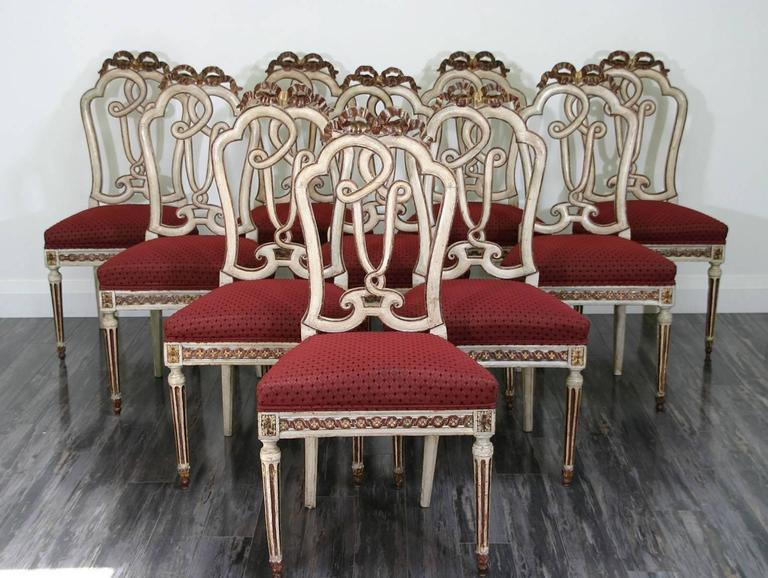 Set of ten Italian Venetian (18th century) painted and gilt trimmed side chairs with open carved back, an upholstered seat and supported by fluted legs.