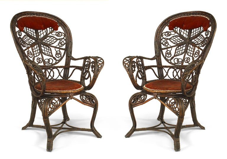 Pair of American Victorian dark stained wicker character fan back arm chairs featuring filigree scroll designs and red velvet upholstered seats and headrests. Manufactured by Colt.