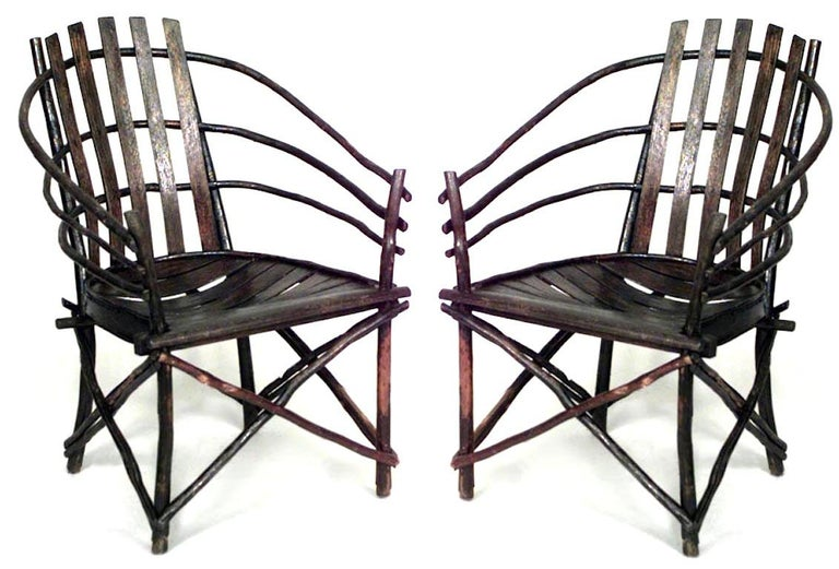 Pair of willow Adirondack armchairs featuring a barrel-back design and slat seats.