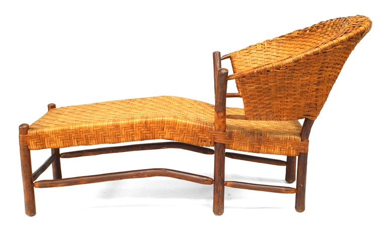 Rustic Old Hickory American chaise longue dating to the turn of the twentieth century. The piece rests upon roughly-hewn logs that support a woven, rounded back and ergonomically-inclined seat.   Since 1899 Old Hickory Furniture has been handcrafted
