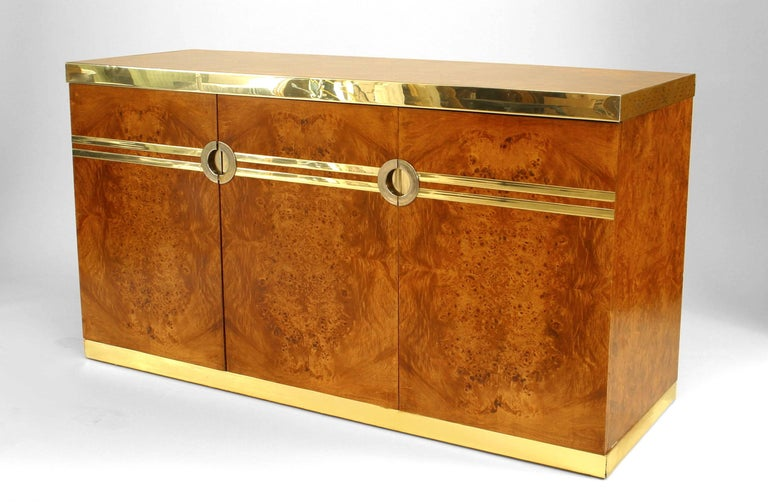 Signed by French designer Pierre Cardin, this burl walnut buffet dates to the 1970's and features three doors, brass trim at its top and base, and two parallel brass strips intercepting two circular handles that provide access to varied internal