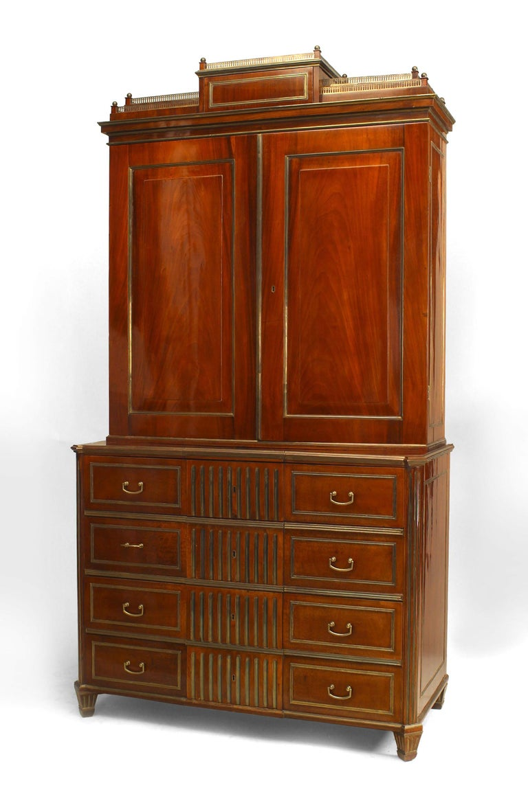 Eighteenth century Russian mahogany secretary bookcase featuring brass accents, including a tiered brass gallery pediment, drawer pulls, and overall trim. In addition to its eight exterior drawers, the piece's two doors and drop front open to reveal