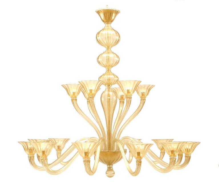 1950's style chandelier by Seguso composed of fluted gold dusted glass with eighteen s-shaped arms holding cup shades, divided between two tiers, one with six arms and the other with twelve.
