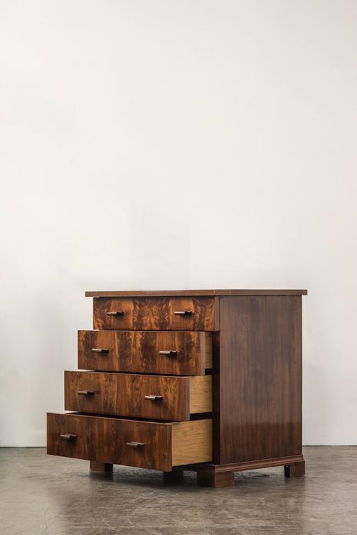 Chest in Fritz Schlegel style veneered walnut with rosewood handles. Drawers gradually get larger as you go down along the chest.  Measures: H 73 cm, D 50.5 cm, W 78 cm. Signs of wear. Offered by ASH NYC.