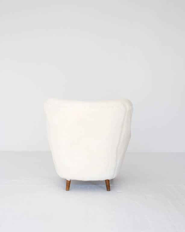 A Fritz Hansen model 1669 easy chair newly reupholstered in sheepskin with original beech legs.