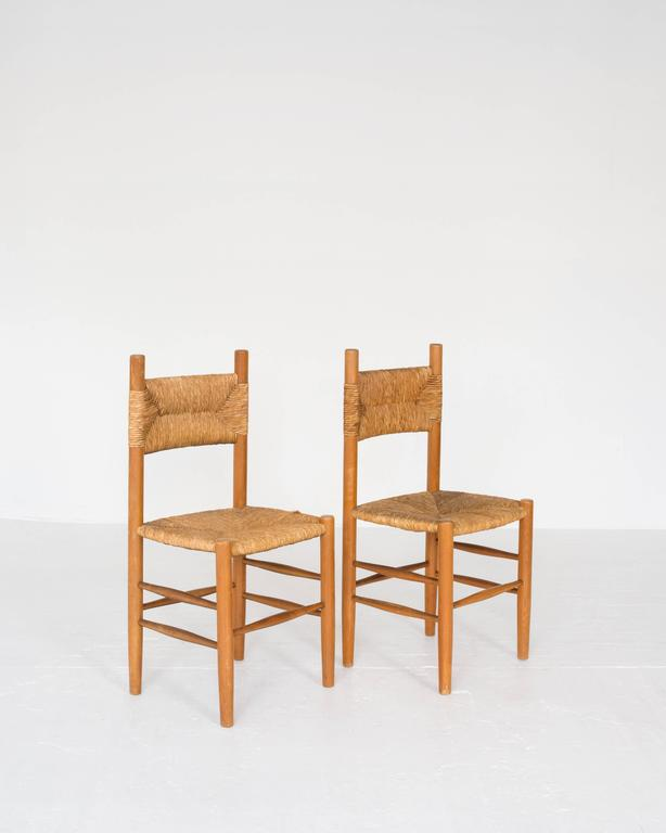 A set of six rush French dining chairs in the style of Charlotte Perriand and Pierre Gautier-Delaye. Offered by ASH NYC.