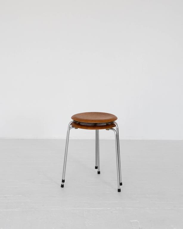 The iconic three-legged stackable stool designed by Arne Jacobsen for Fritz Hansen. Two available.