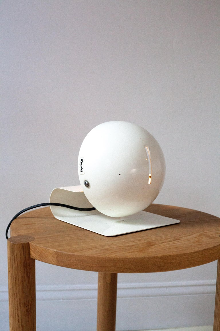 A white powder coated table lamp by Guzzini, Italian, 1960s. The metal shade tilts and they have been adapted to wall sconces though this lamp has a euro plug and switch.