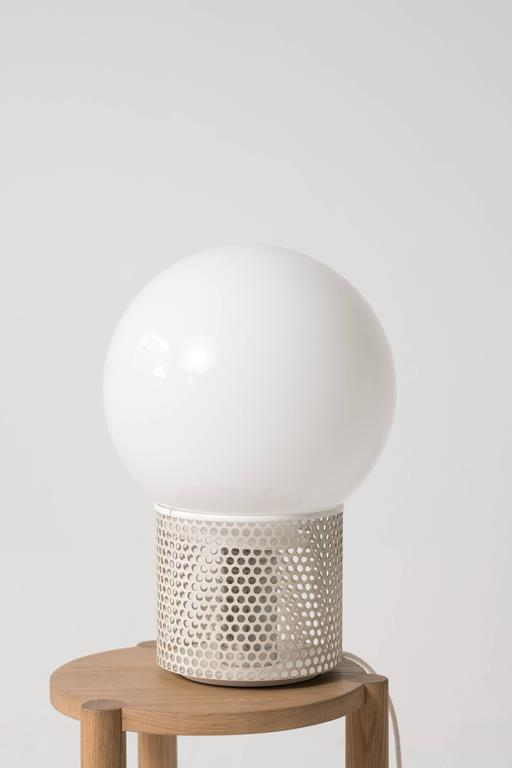 A very large orb lamp by Michel Boyer with a white lacquered perforated metal base.   The light has been rewired with a US plug and is fully functional with a new LED light bulb.