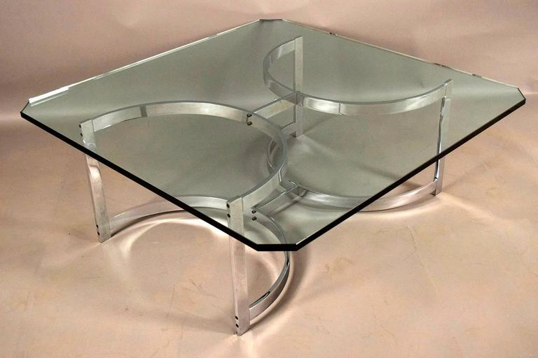 This 1970s Mid-Century Modern coffee table features a square clear glass top with clipped corners. The chrome base features a half circle stretched pedestal legs that gives the coffee table a unique look. The coffee table is ready to be used and