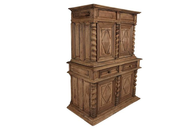 This early 19th century French Renaissance-style buffet is made of solid walnut wood with a beautiful bleached finish. The top section is beautifully carved with three carved twisted columns framing the two doors with carved panels with geometric