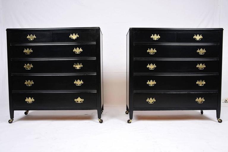This 1920s antique Regency-style pair of chest of drawers is made from mahogany wood that has been finished in a rich black color stain. These elegant chest of drawers feature two side by side top drawers and four full size drawers below. The facade