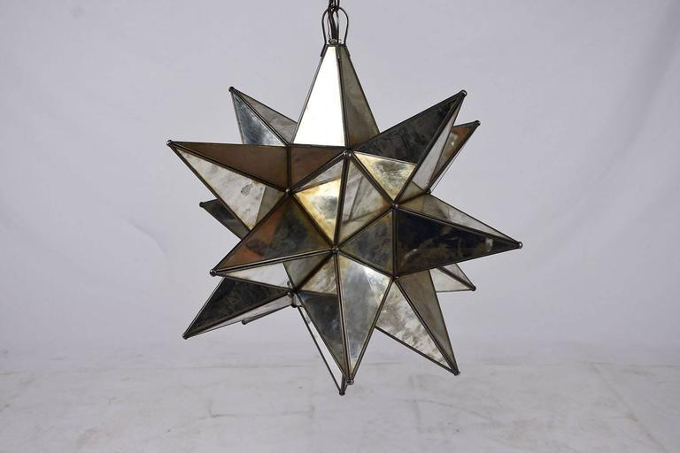 This 1980s Contemporary Modern-style chandelier is in an eye-catching starburst design. The star points are adorned with distressed mirrors separated by metal pieces. A section lifts up to reveal where the light is housed. The interior light