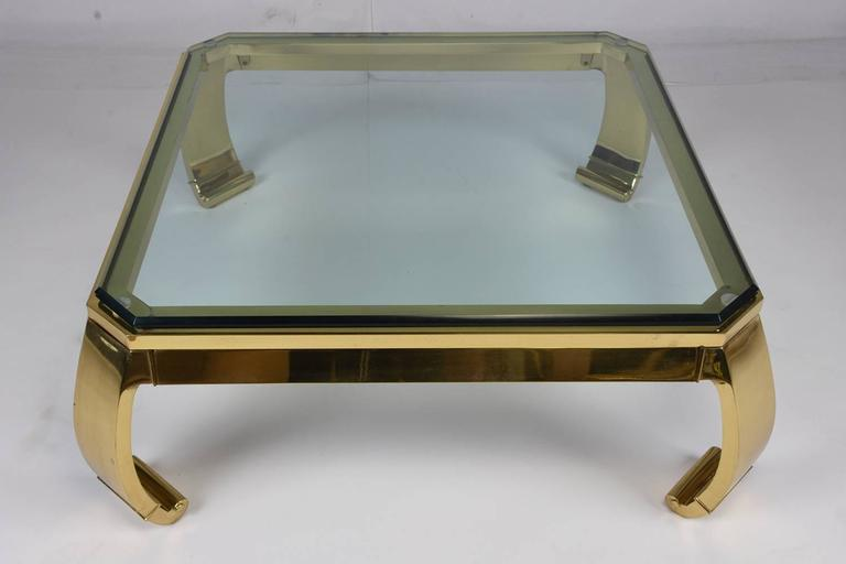 This 1960s vintage Hollywood Regency style coffee table features a frame made from brass and an inserted beveled glass top. The unique legs are tapered and end with a scroll toe with a delicate moulding detail. This coffee table is sturdy, stylish,