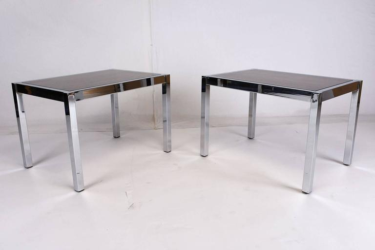 This pair of 1970s Mid-Century Modern style side tables feature a simple, but elegant chrome frame. The base is highlighted by a rosewood top with a rich stain and a lacquered finish. This pair of side tables is sturdy, stylish, and ready to be used