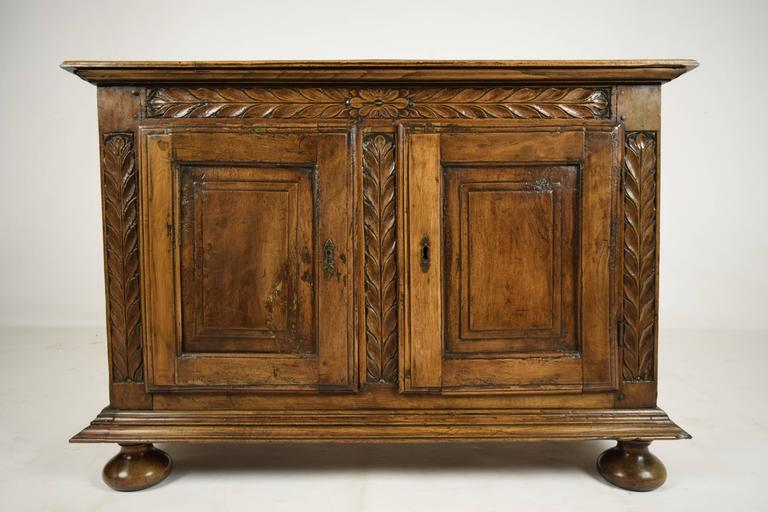 This late 18th century Provincial style sideboard is made of walnut wood that features its original walnut wood finish. The sideboard features a beveled edge wood top and carved floral motif mouldings throughout. There are two cabinet doors that