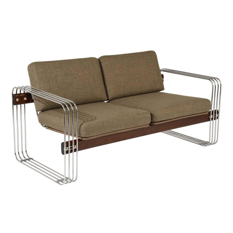 This 1950s Mid-Century Modern-style sofa is designed by Heinz Meier and features a chromed steel base with wood accents. The wood has been stained in a walnut color with a lacquered finish. The removable cushions have recently been professionally
