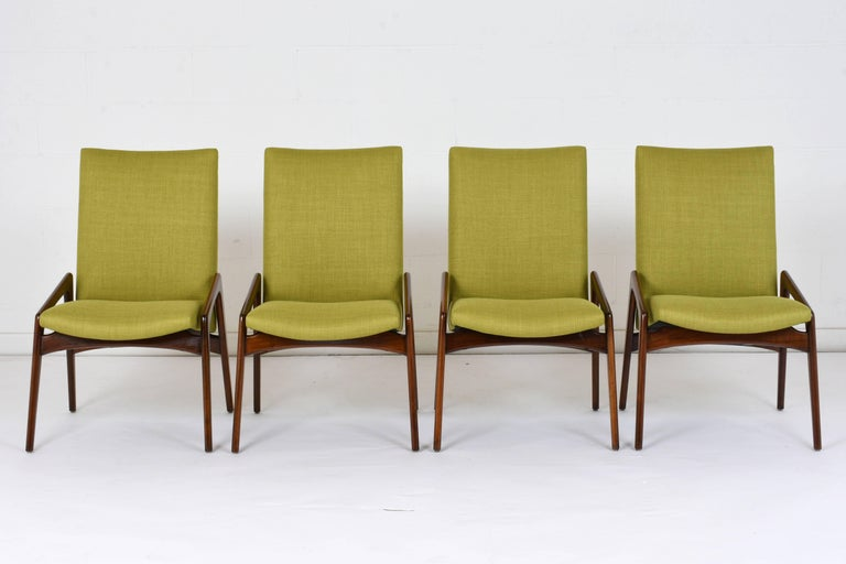 This set of four 1960s Danish Mid-Century Modern style dining chairs are designed by Kai Kristiansen. The geometric teak wood frames are finished in a walnut color with a lacquered finish. The seats have recently been professionally upholstered in a