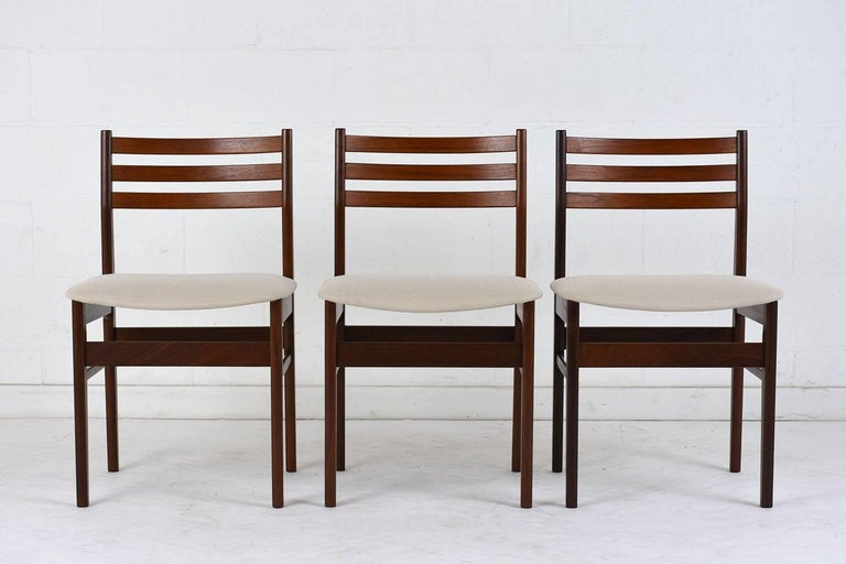 This set of six 1960s Danish dining chairs feature rosewood frames finished in a rich rosewood color with a polished finish. The frames have a slat design on the seat back and stretched tapered legs. The comfortable seats have been completely