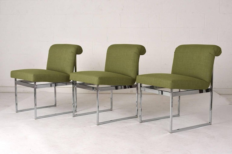 This set of six 1960s Mid-Century Modern style dining chairs are in the style of Milo Baughman. The chairs have a simple geometric chrome frame that pairs well with the upholstered seat. The seat has a unique shape with a scroll curved back and a