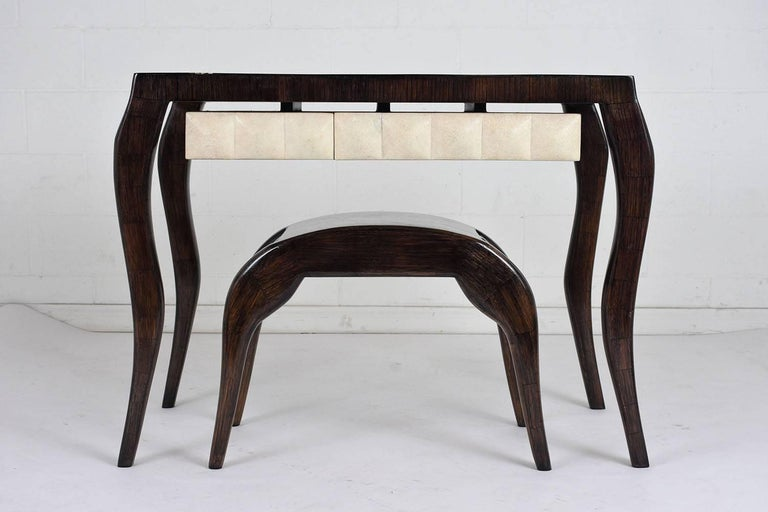 This 1980s Modern-style dressing table and bench set is made by R & Y Augousti, Paris. The table and bench are made from carved wood stained in a deep ebony color with a lacquered finish. The legs of the desk are carved in a serpentine shape and are