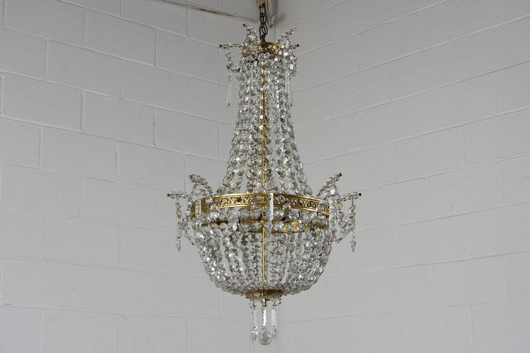 This stunning 1900s Hollywood Regency-style basket chandelier is made of brass with crystal accents. The upper and center bands have leafy cut-out decorations and the bottom band is decorated with carved fabric swags and tassels. The chandelier is
