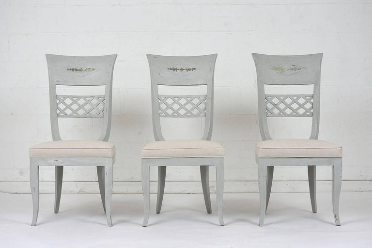 This set of six 1970's Hollywood Regency-style dining chairs feature painted wood frames in a soft gray and off-white color combination and a distressed finish. The high back of the chairs have a lattice splat and inlaid brass accents at the top.