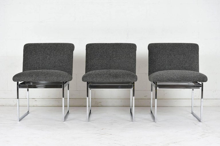This set of six 1960s Mid-Century Modern style dining chairs are in the style of Milo Baughman. The chairs have a sleek chrome frame with professionally upholstered seats. The seats have a scroll back with a heathered grey color fabric with a