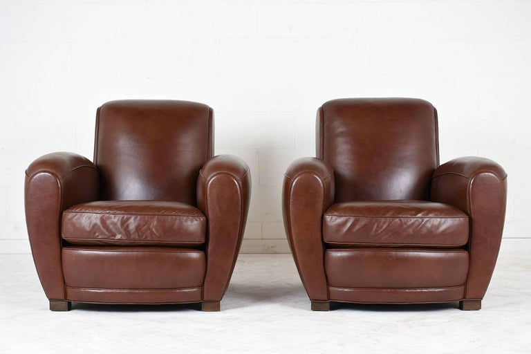 This pair of 1930's French Art-Deco-style club chairs features the original brown leather upholstery with single piping trim details and brass nail head trim on the back. The chairs are in excellent condition with a single seat cushion that is very