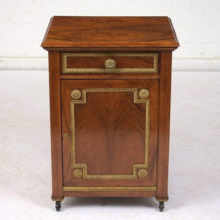 This 1890s French Louis XVI-style nightstand is cover in walnut veneers with the original finish. The drawer and cabinet door are adorned with the original brass decorative moulding with rosettes in the corners and on the knobs. Inside the cabinet