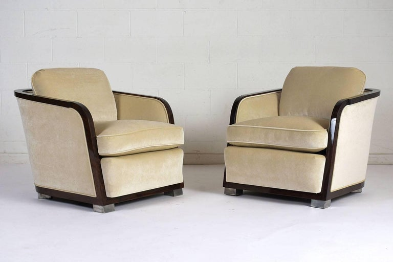 This pair of 1960s Art Deco-style club chairs have a curved profile with a rosewood color wood frame with a lacquered finish. The chairs are upholstered on the back, seat, and front edge in a beige color velvet fabric with single piping trim