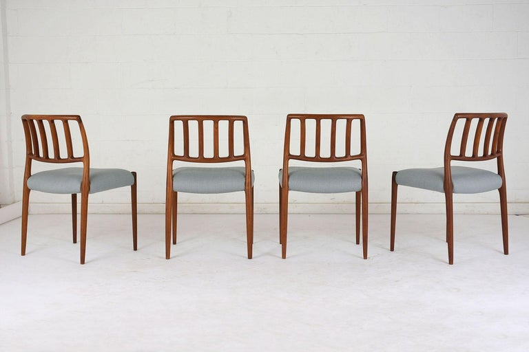 This set of six 1960s Mid-Century Modern dining room chairs is model 83 by Niels Otto Moller. The teak wood frames have a curved back with slatted accents and the original finish. The comfortable seats have been completely restored with new cushions
