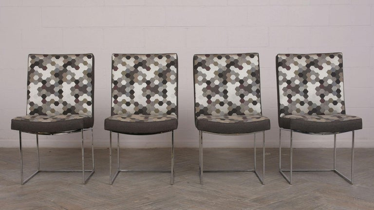 Set of 8 modern dining chairs. Chairs have a solid chrome square frame with curve seat. All chairs have been professionally reupholstered in a solid dark gray color on the back, sides, and front. The back and seat have a multicolored symmetrical