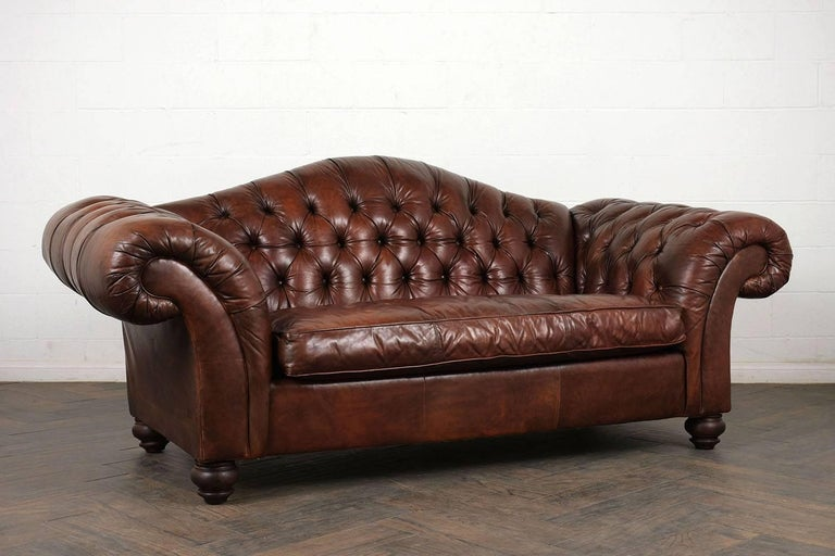 This 1970s Chesterfield sofa has a camel back profile with exaggerated scroll arms. The sofa is upholstered in a rich brown color with tufted details on the back and arms with single piping trim details. There is a single comfortable cushion that