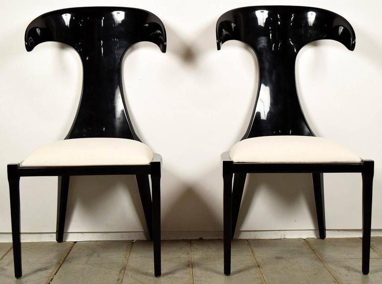 Set of two Anvil design backs, Italian modern dining chairs, solid wood frames, finished in a rich black lacquered color. Seats have been professionally upholstered in a chenille ivory color. Chairs are in great condition, strong and sturdy, ready