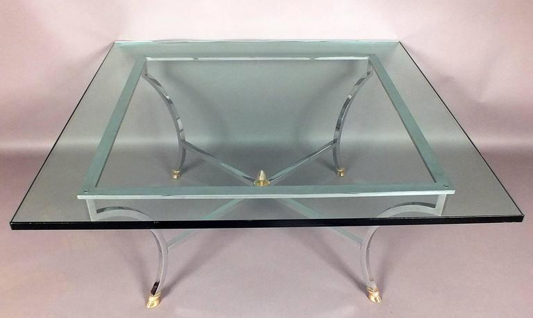 This 1970's Vintage Hollywood Regency-style coffee table features a square glass top that is 3/4 inches thick with a flat polish finish. Holding up the glass is a sleek square brass frame in a chrome color with X-shaped stretched legs and a finial