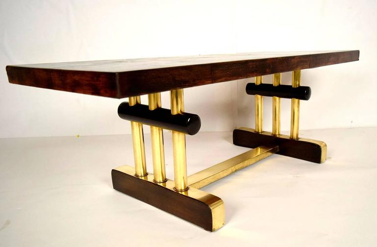 French 1950s modern coffee table. Has original refurbished brown distressed leather top. Bronze and wood pedestal legs with three columns on each side black cylinder on top of the columns. On the right side on the wooden leg you will see a plaque
