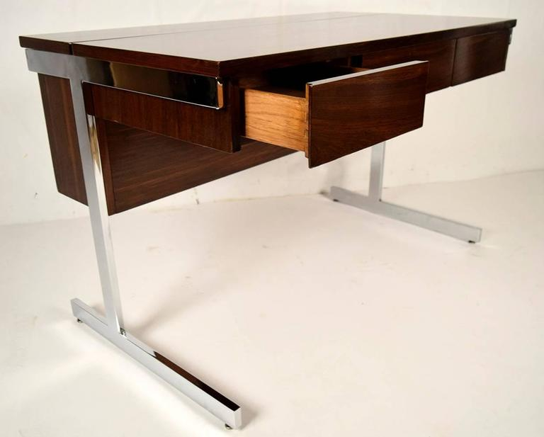 This elegant Mid-Century Modern-style desk is made from solid rosewood with its original rosewood finish. There are three front side-by-side pullout drawers and a flush lift-top compartment at the back that can be used for files or storage. The desk