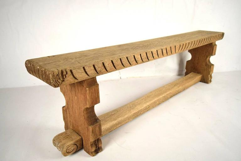 This is a beautiful 1890's hall bench made of solid oak wood in a bleached wood color. The bench is adorned with hand-carved designs on the sides, and the stretched legs. This bench is solid and sturdy, ready to be used for years to come.