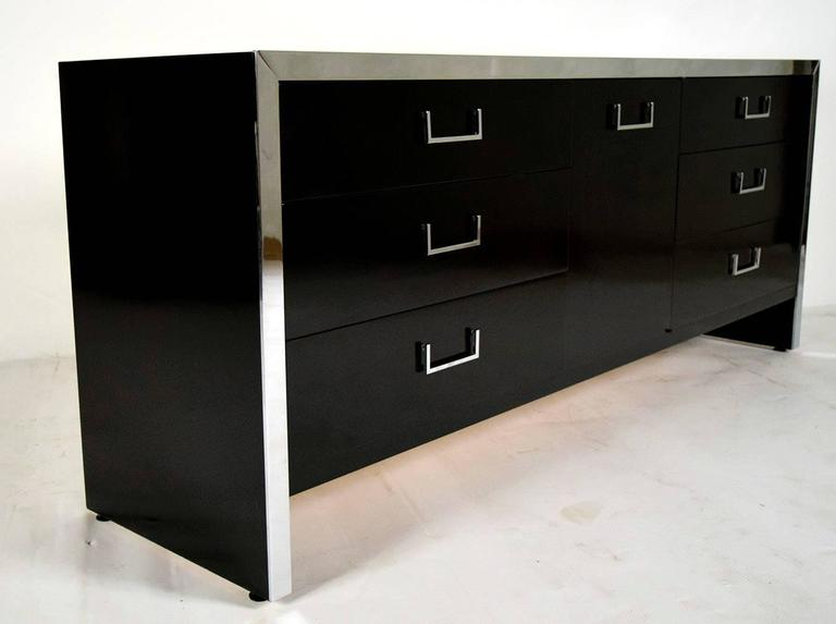 Modern 1970's credenza or chest of drawers. Solid wood, newly finished in a rich deep black lacquered color. Features three sections, sides have three drawers with steel handles, the center has one door with top steel handle and three pullout