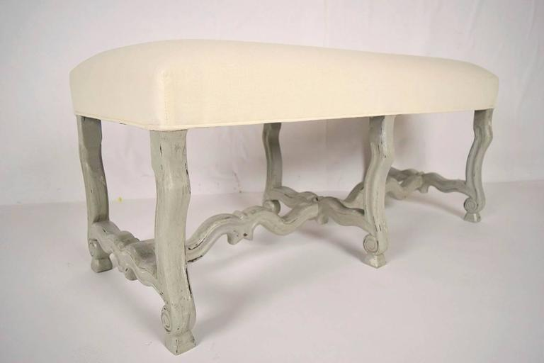 This is a 1970s French Provincial style bench. Solid walnut wood, newly painted in a gray color with a distressed finish. Seat has been newly upholstered in an off-white color linen fabric. Bench is ready to be used.