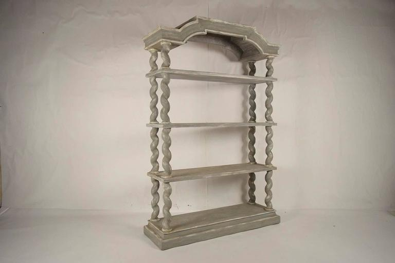 This large 1970s four-tier etagere or bookshelf is made of solid wood and is recently painted in a grey and oyster color combination with a distressed finish. The elegant pediment on top is supported by thick twisted supports and ha three thick