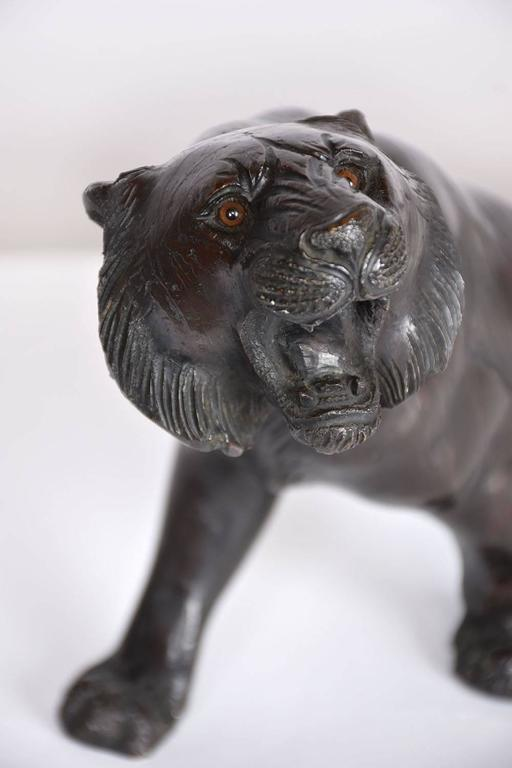 This 1930s Hollywood Regency-style tiger sculpture is made of bronze. The statue depicts the tiger striding forward and mid-roar. The attention to detail does not go unnoticed in the stripes on the fur and in the face. This tiger statue is solid,