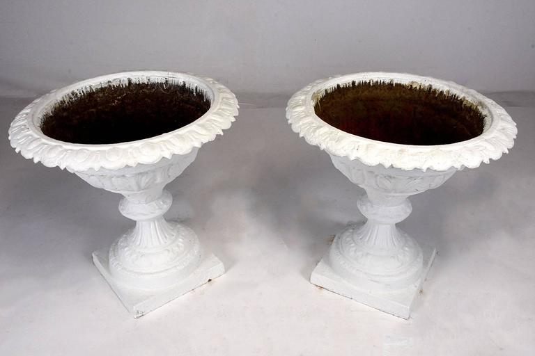 This pair of large planters is made from cast iron that has been painted in an off-white color. The planters are beautifully adorned with floral motif designs on the lip, egg and dart decorative band, fleur-de-lis designs, and architectural