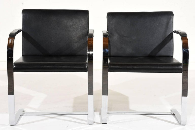This pair of 1960s Mid-Century Modern flat bar Brno chairs by Mies Van Der Rohe feature a sleek chrome frame and leather upholstery. The floating frame is sturdy and supported by a stretched bar at the bottom. The seat and arm rests feature the
