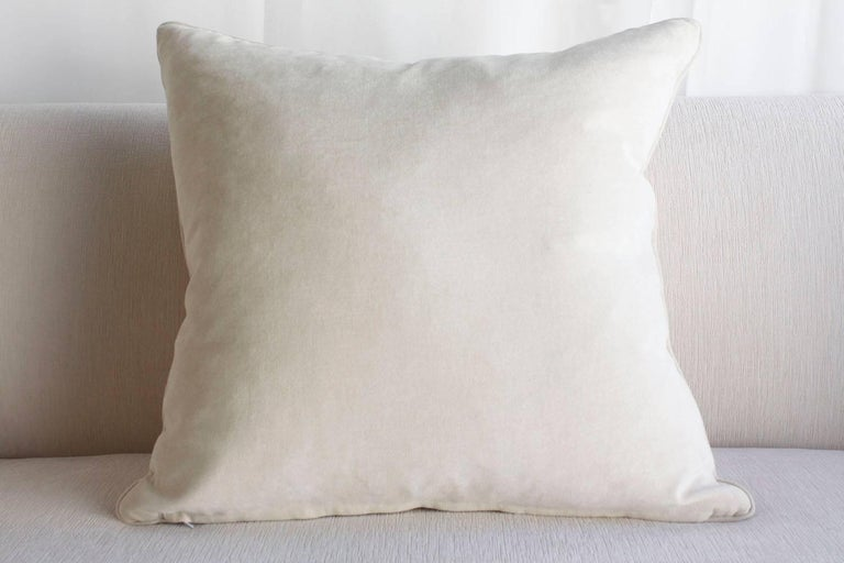 This pair of French Louis XVI-style throw pillows are made with a raised floral and leafy pattern from the early 1900s. The back features an ivory colored velvet with single piping trim details. Inside there is a comfortable down pillow insert. This