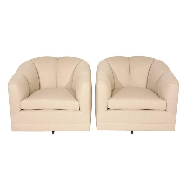This pair of 1960s Mid-Century Modern-style swivel chairs are upholstered on all sides in a beige color fabric. The curved backs and arms feature a channel design that accents the profile of the chair. The seat is made from a comfortable new foam