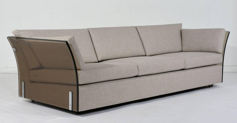 This 1960s, Mid-Century Modern style sofa is designed by Milo Baughman. This unique sofa features curved Lucite side panels accented by large steel brackets. The seat has recently been professionally upholstered in a sand color fabric with single